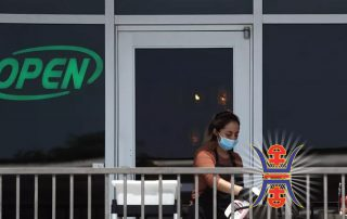 A restaurant employee cleans an outdoor patio table at Benny's Cafe in Colleyville on April 27, 2020, prior to a reopening of businesses in Texas.